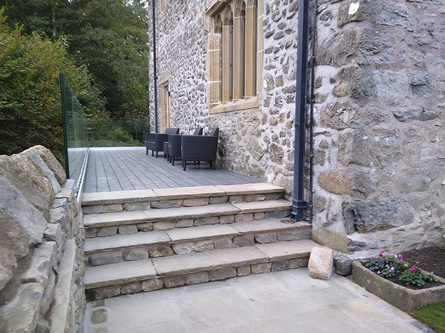 Solid grey decking with outdoor chairs